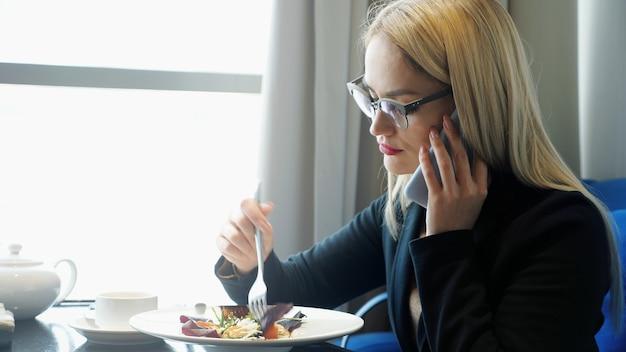 Manager di giovane donna che parla al telefono e mangia durante una pausa al bar.