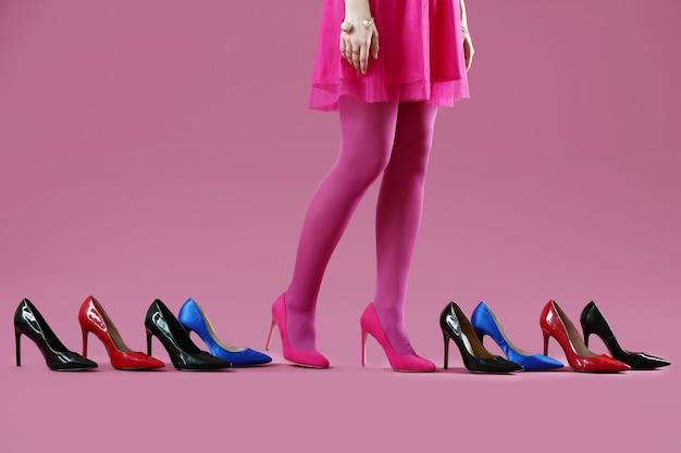 Giovane donna e molte scarpe alla moda su sfondo colorato