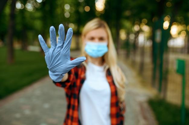 Giovane donna in maschera e guanti nel parco, quarantena. persona di sesso femminile che cammina durante l'epidemia, assistenza sanitaria e protezione, stile di vita pandemico