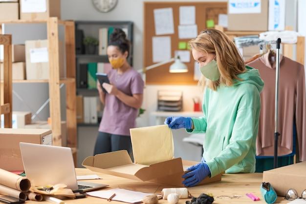 Giovane donna in maschera pacco di imballaggio mentre in piedi vicino al tavolo con il suo collega nel muro in officina