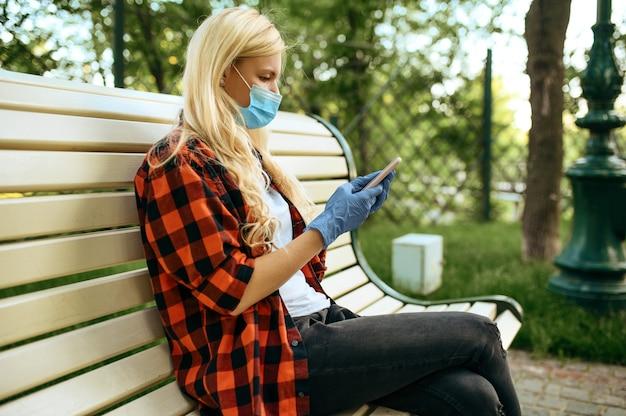 Giovane donna in maschera seduta su una panchina nel parco, quarantena. persona di sesso femminile che cammina durante l'epidemia, assistenza sanitaria e protezione, stile di vita pandemico