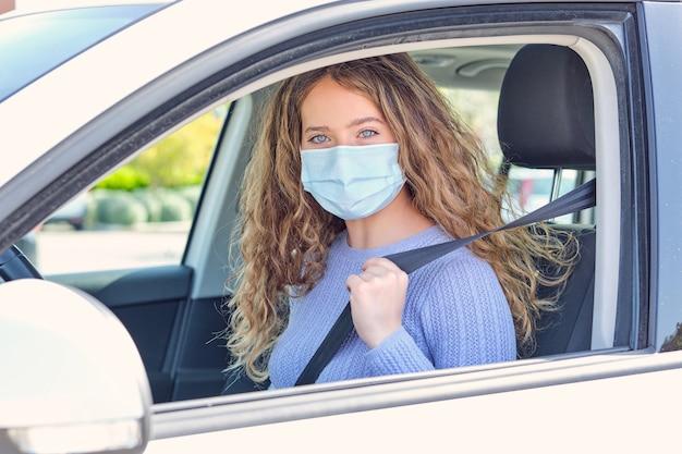 Giovane donna in maschera seduta sul sedile del conducente dell'auto