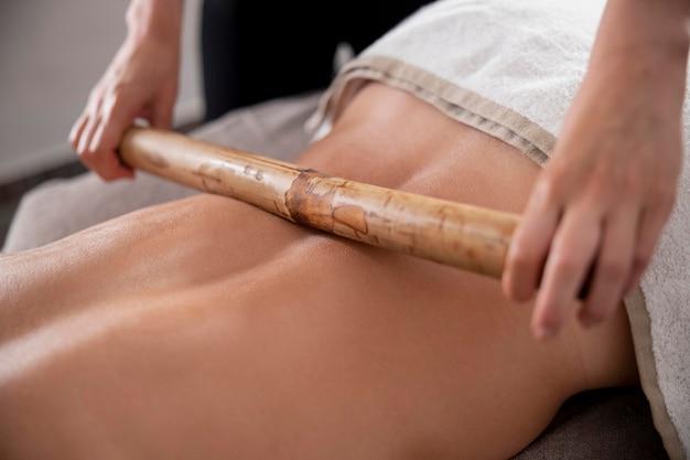Giovane donna che massaggia il suo cliente nel suo salone