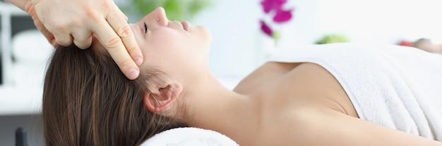 Il massaggiatore della giovane donna fa un massaggio rilassante alla testa