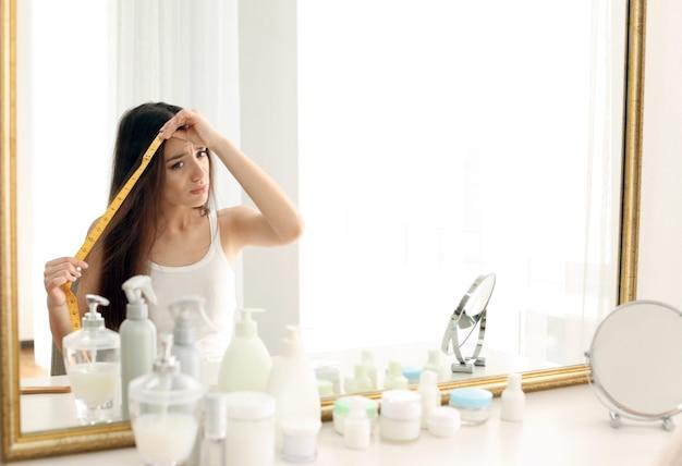 Giovane donna che misura la lunghezza dei capelli davanti allo specchio a casa