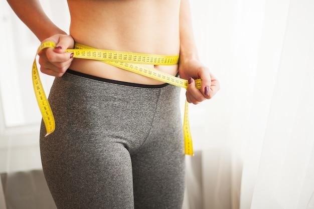 Giovane donna che misura la sua vita con nastro adesivo