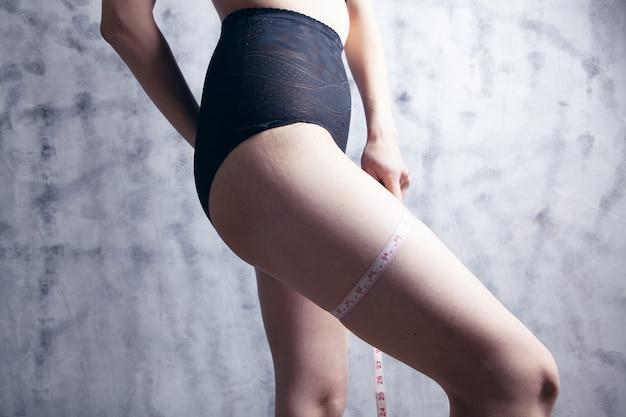 Giovane donna che misura la circonferenza della gamba