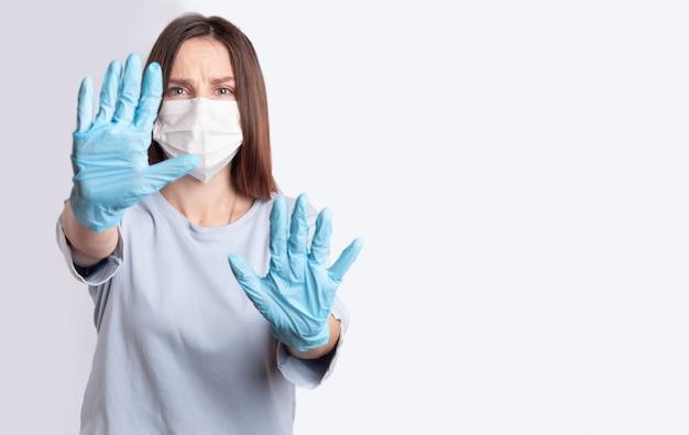 Giovane donna in maschera monouso medica e guanti in lattice blu su uno sfondo grigio-blu.