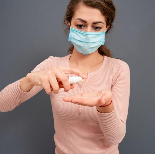 Giovane donna con maschera medica sul viso che usa gel igienizzante per disinfettarsi le mani su una superficie grigia