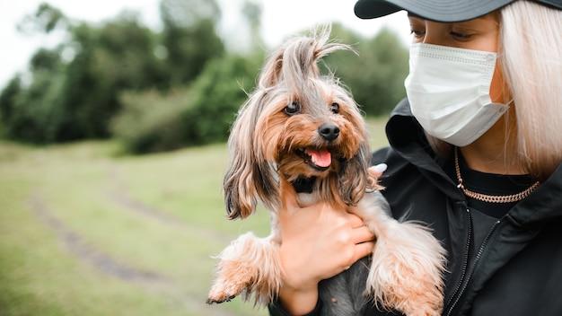La giovane donna in una mascherina medica tiene un piccolo cane tra le sue braccia