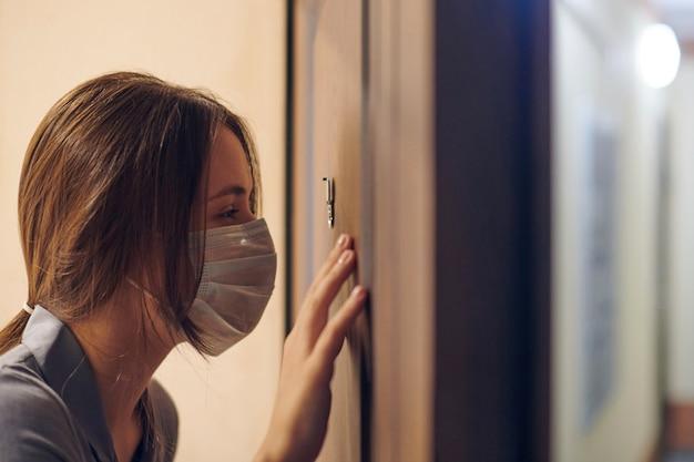 Giovane donna in maschera medica guardando attraverso lo spioncino della porta d'ingresso in appartamento quando qualcuno suona il campanello. rimanere a casa e il concetto di auto isolamento
