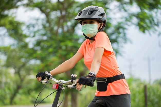 Una giovane donna in maschera medica va in bicicletta