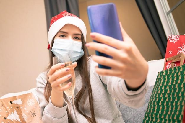 Una giovane donna con una maschera medica e un cappello da babbo natale a casa si congratula con i suoi amici per natale e capodanno tramite smartphone, babbo natale con un bicchiere di champagne