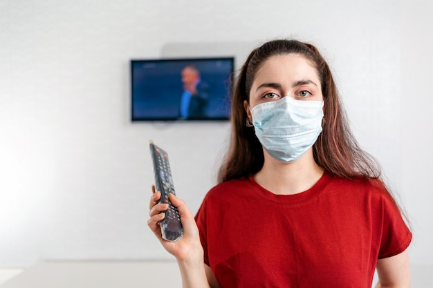 Una giovane donna con una maschera medica accende il telecomando della tv