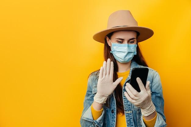 Giovane donna in guanti sterili medici maschera viso, utilizzando smartphone, chattando con gli amici, leggendo e-mail con buone notizie, navigazione web, indossa giacca di jeans e cappello, isolato su sfondo giallo.
