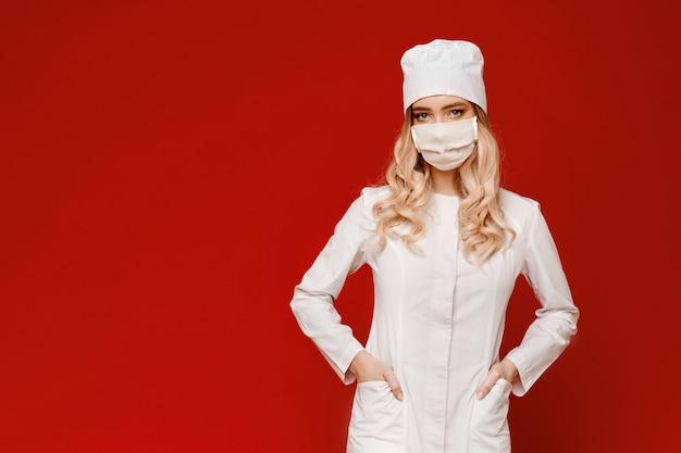 Giovane donna in uniforme medica e maschera protettiva in posa su uno sfondo rosso, isolato con spazio di copia a sinistra. gente di sanità professionale e concetto della medicina