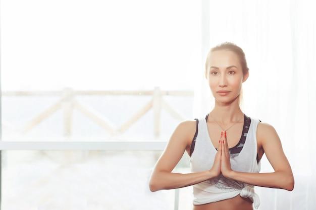 La giovane donna medita mentre pratica lo yoga nella posa del loto libertà calma e relax concept