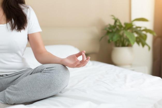 Giovane donna che medita, fa yoga e si rilassa a letto a casa