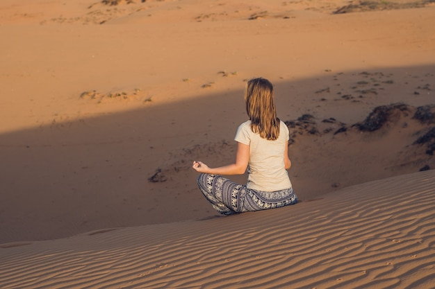 Giovane donna meditando nel deserto sabbioso rad al tramonto o all'alba