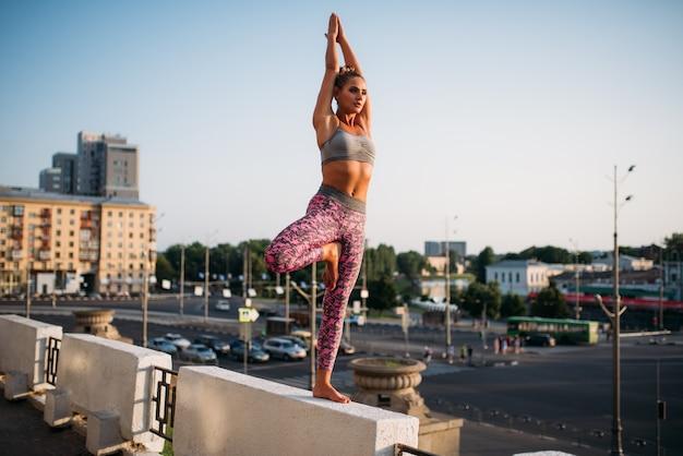 Giovane donna meditando in posa yoga, esercizio di equilibrio, città. yogi allenamento all'aperto