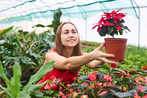 Giovane donna nel mezzo di una serra sorridente porge un fiore rosso