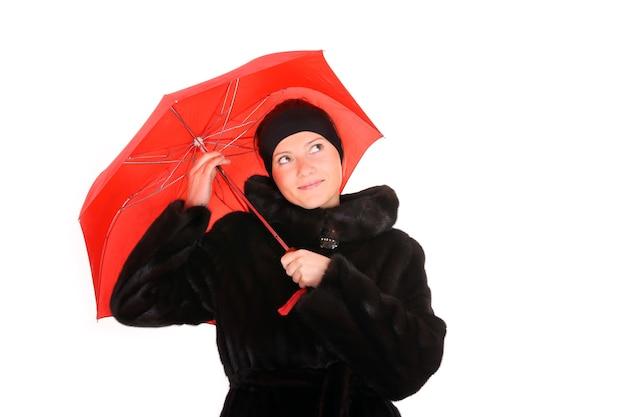 Una giovane donna in una pelliccia di visone con un ombrello rosso sorridente su bianco
