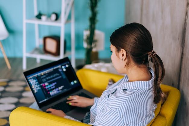 Sviluppatore mobile di giovane donna con laptop, scrive il codice del programma su un computer, il programmatore lavora in un ufficio moderno.