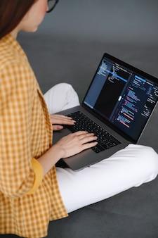 Lo sviluppatore mobile della giovane donna scrive il codice del programma sul lavoro di un programmatore di computer