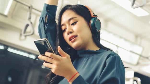 Telefono cellulare della giovane donna sul treno pubblico