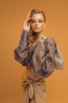 Modello di giovane donna in abiti alla moda, foto studio verticale su sfondo beige. foto di alta qualità