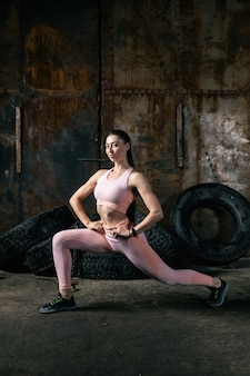 Modello di giovane donna in un top corto sportivo e leggings da palestra fa affondi per i piedi in avanti, le mani sono tenute alla vita in un vecchio garage