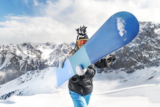 Giovane donna in cappello mohawk che tiene uno snowboard di fronte a lei. le migliori riprese sportive epiche con spazio di copia