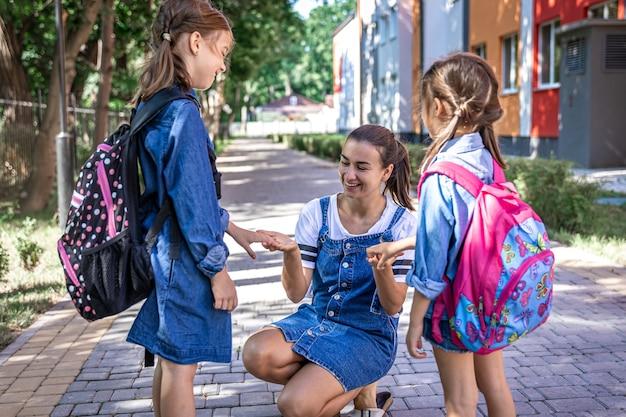 Una giovane donna sostiene moralmente le figlie tenendosi per mano incoraggia i bambini, accompagna gli studenti a scuola.