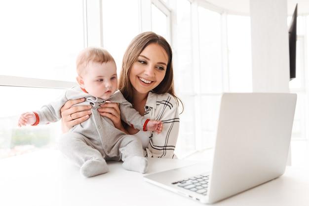 Madre della giovane donna che utilizza computer portatile con il suo bambino piccolo