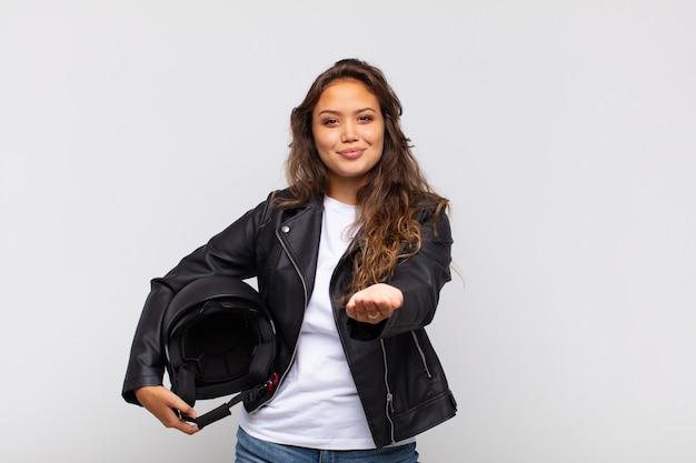Motociclista della giovane donna che sorride felicemente con uno sguardo amichevole, fiducioso, positivo, offrendo e mostrando un oggetto o un concetto