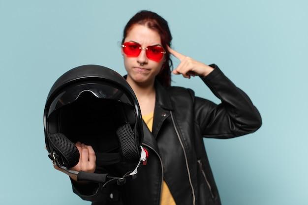 Motociclista di giovane donna con un casco di sicurezza