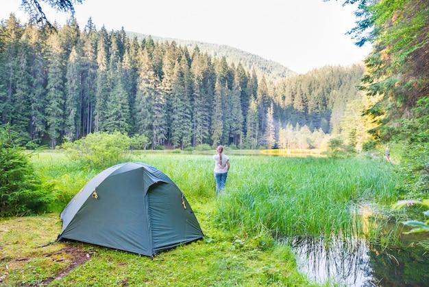 Giovane donna vicino alla tenda verde e al lago forestale in montagna con acqua blu