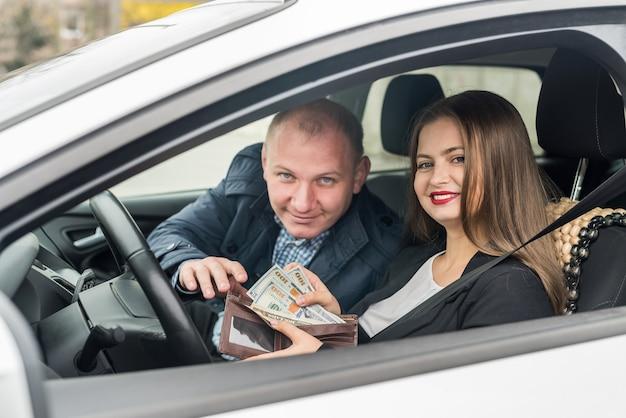 Giovane donna che offre dollari attraverso il finestrino dell'auto
