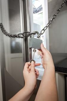 Giovane donna che apre la serratura del frigorifero con una chiave grande
