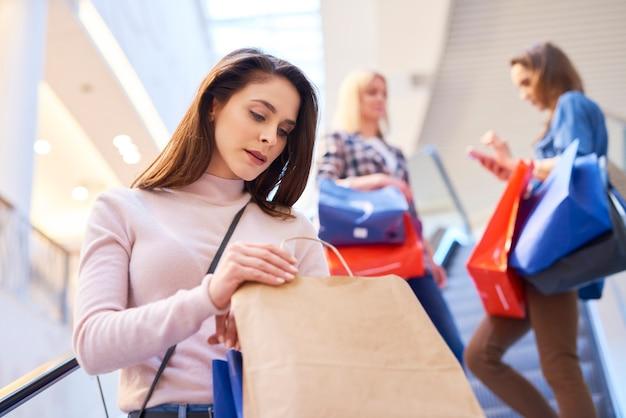 Giovane donna che apre la borsa della spesa nel centro commerciale