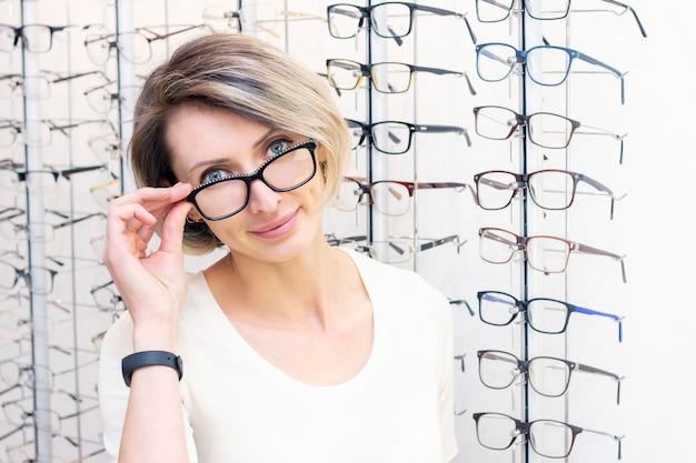 Giovane donna in negozio di ottica scegliendo nuovi occhiali con ottico. occhiali nel negozio di ottica. una donna sceglie gli occhiali. emozioni. oftalmologia.