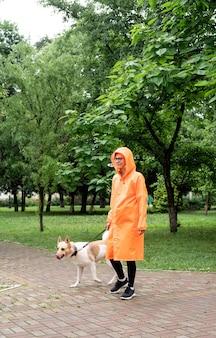 Giovane donna in impermeabile arancione che cammina con il suo cane in un parco