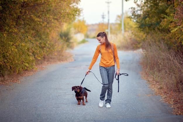 Giovane donna in un dolcevita arancione e jeans cammina con un cane al guinzaglio in un parco in autunno