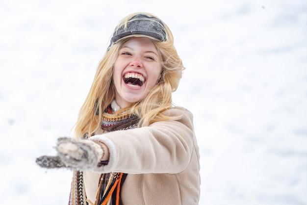Giovane donna all'aperto giocando a palle di neve lotta