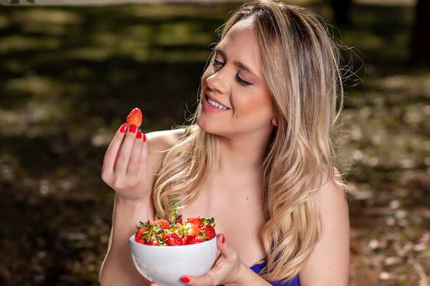 Giovane donna all'aperto sotto gli alberi in un parco, felice e sorridente, facendo pic nic e degustazione di fragole.