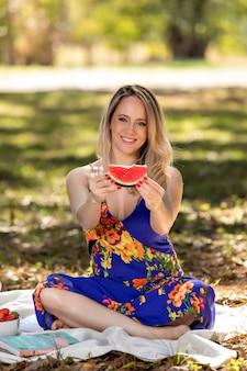 Giovane donna all'aperto sotto gli alberi in un parco, felice e sorridente, facendo pic nic e degustazione di anguria.