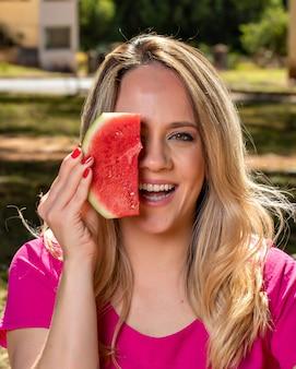 Giovane donna all'aperto sotto gli alberi in un parco, felice e sorridente, facendo picnic e degustazione di anguria e offrendo una fetta.