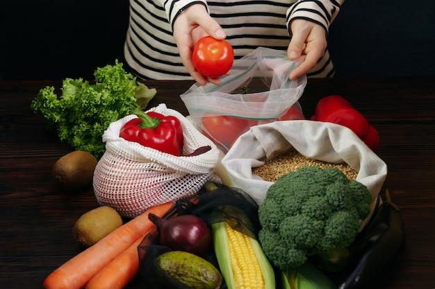 Giovane donna che imballa le verdure organiche fresche in sacchetti di eco sulla tavola di legno.
