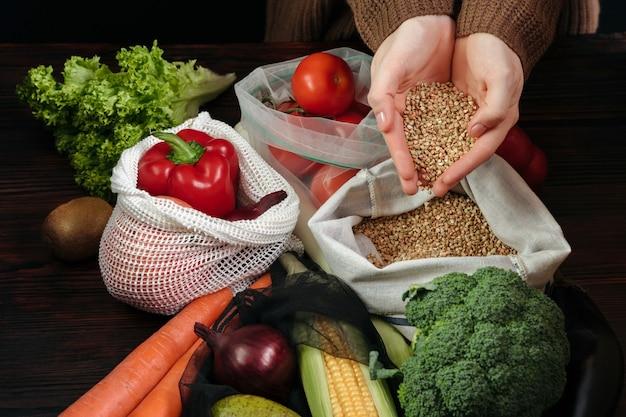 Giovane donna che imballa verdure organiche fresche in sacchetti di eco sulla tavola di legno