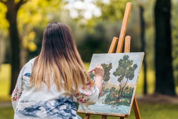 Giovane donna che dipinge su tela nel mezzo di un parco.